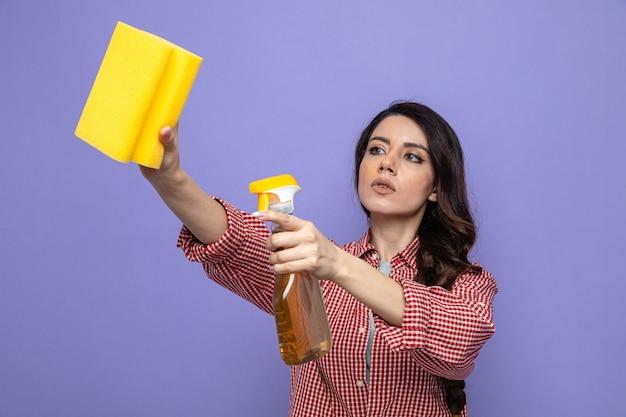 Femme de nettoyage assez caucasienne confiante tenant un nettoyant en aérosol et une éponge regardant de côté