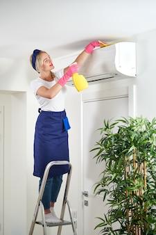 Femme de nettoyage du climatiseur avec un chiffon. service de nettoyage ou concept de femme au foyer