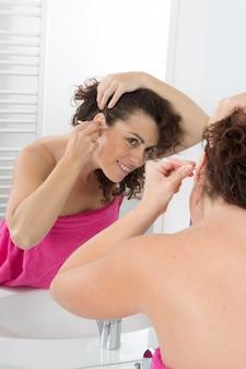 Femme, nettoyage, oreilles, coton, tige, salle bains