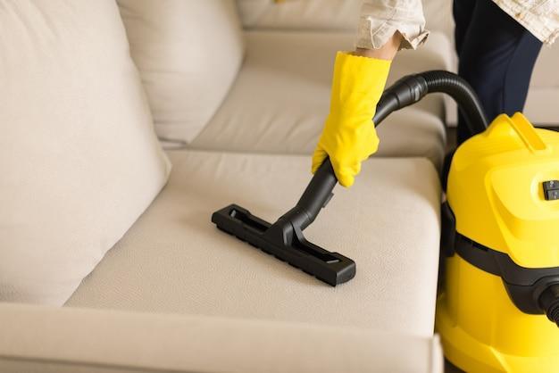 Femme nettoyant un canapé avec un aspirateur jaune. espace de copie. concept propre