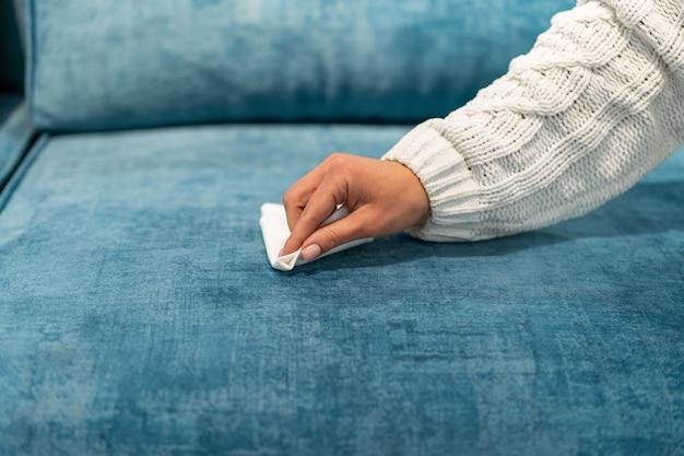 Femme nettoyant un canapé bleu avec un chiffon blanc