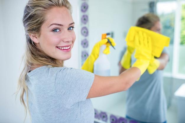 Femme nettoyant le miroir dans la salle de bain
