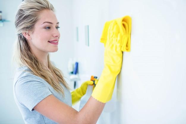Femme nettoyant la salle de bain dans sa maison