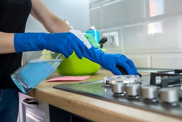 Femme nettoyant la surface du gaz en acier inoxydable dans la cuisine avec des gants en caoutchouc.