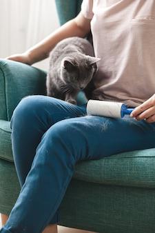 Femme nettoyant les vêtements avec un rouleau collant à partir de poils de chat.