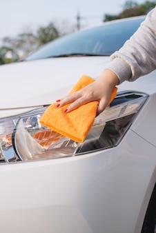 Une femme nettoyant une voiture avec un chiffon en microfibre, un concept d'esthétique automobile (ou de voiturier)