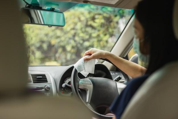 Femme nettoyant le volant avec un chiffon humide dans une pandémie de coronavirus de voiture