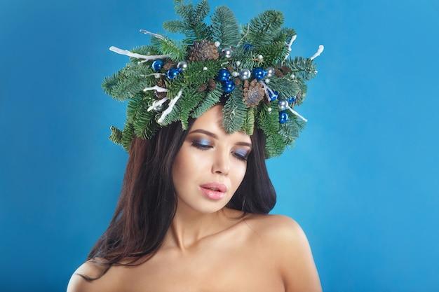 Femme de noël. belle coiffure de nouvel an et arbre de noël vacances et maquillage.