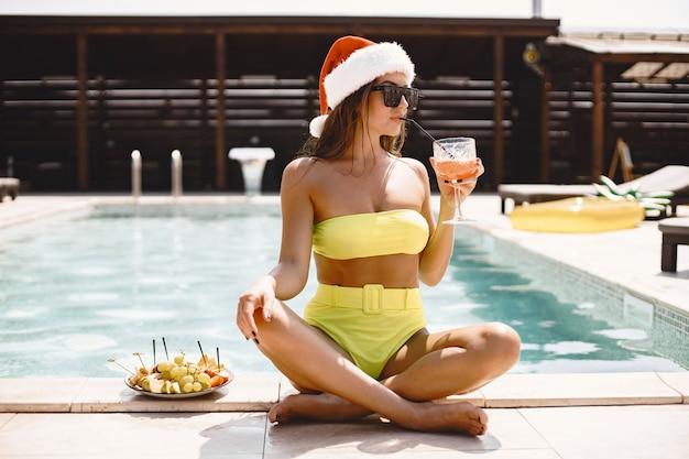 Femme de noël relaxante au bord de la piscine. fille drôle célébrant noël dans une station balnéaire. avec cocktail et fruits.