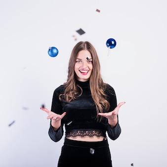 Femme en noir lançant des boules brillantes