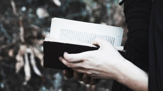 Femme en noir avec livre ouvert