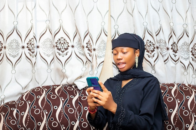 Femme noire africaine excitée utilisant son téléphone portable la bouche grande ouverte après avoir reçu de bonnes nouvelles des médias sociaux