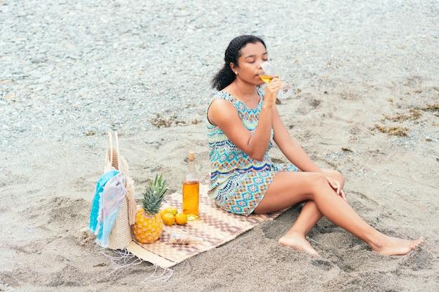 Femme noire appréciant un verre de vin sur la plage le matin