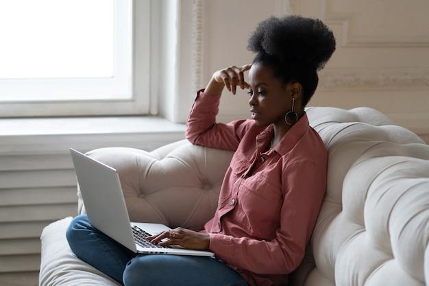 Femme noire assise sur un canapé parlant sur un chat vidéo en ligne ou un webinaire à la maison en train de discuter avec un ordinateur portable