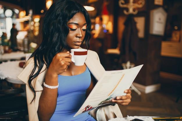 Femme noire assise dans un café