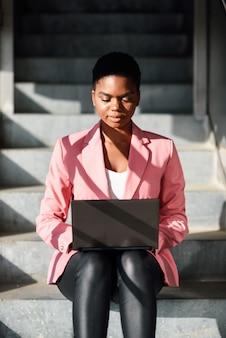 Femme noire assise sur des marches urbaines travaillant avec un ordinateur portable.