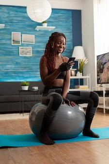 Femme noire athlétique sportive relaxante sur un ballon de stabilité vérifiant les médias sociaux à l'aide d'un smartphone après un exercice d'entraînement intense, dans le salon de la maison, assise sur un tapis de fitness pour la force musculaire.
