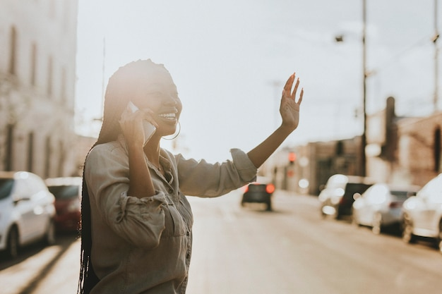 Femme noire au téléphone hélant un taxi