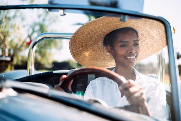Femme noire au volant d'une voiture décapotable vintage