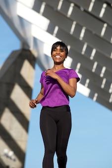 Femme noire en bonne santé en cours d'exécution à l'extérieur et souriant