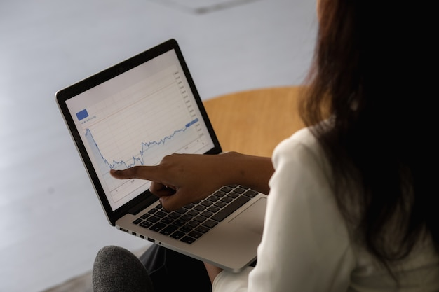 Une femme noire concentrée dans un costume travaille sur un ordinateur portable à distance de la maison