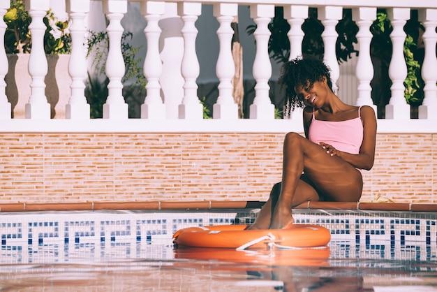 Femme noire dans une piscine avec bouée de sauvetage