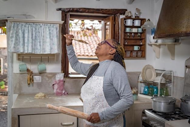 Une femme noire danse et chante joyeusement tout en cuisinant dans une cuisine vintage traditionnelle