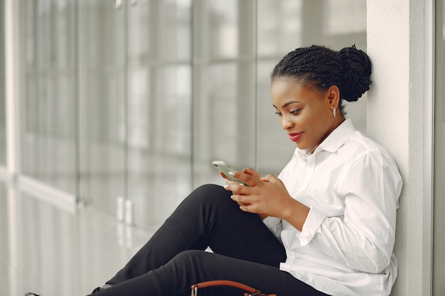 Femme noire, debout, dans, bureau, à, a, ordinateur portable