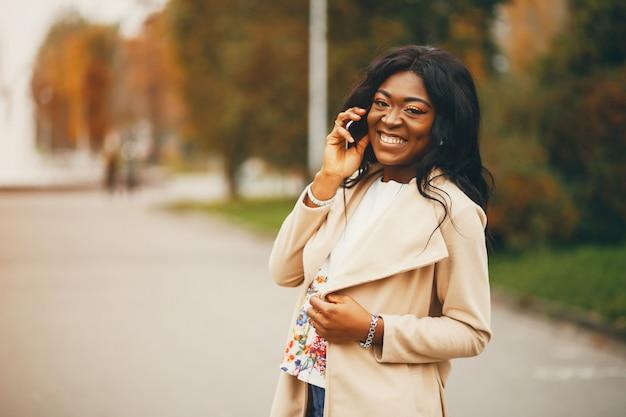 Femme noire debout dans une ville d'automne