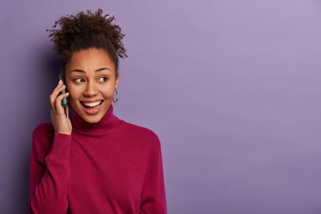 Une femme noire heureuse a une conversation téléphonique, regarde de côté, discute de nouvelles agréables avec un ami proche, appelle quelqu'un, porte un col roulé bordeaux