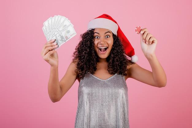 Femme noire avec jeton de poker casino et argent liquide portant un chapeau de vacances sur rose