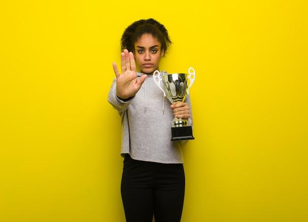 Femme noire jeune fitness mettant la main devant. tenant un trophée.