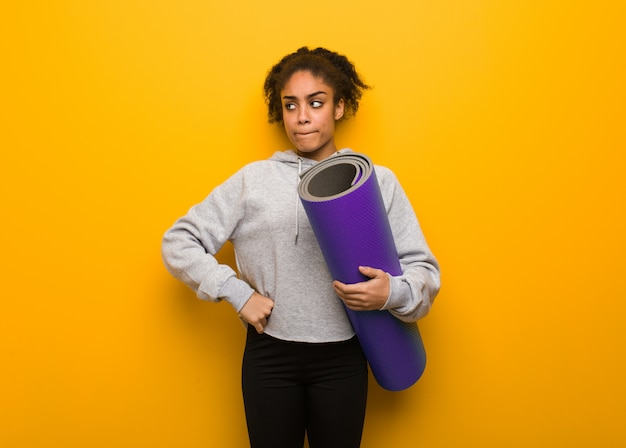 Femme noire jeune fitness pensant à une idée. tenant un tapis.