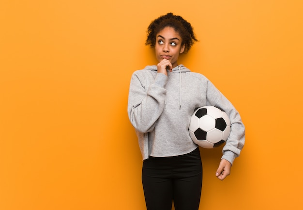 Femme noire jeune fitness pensant à une idée. tenir un ballon de foot.