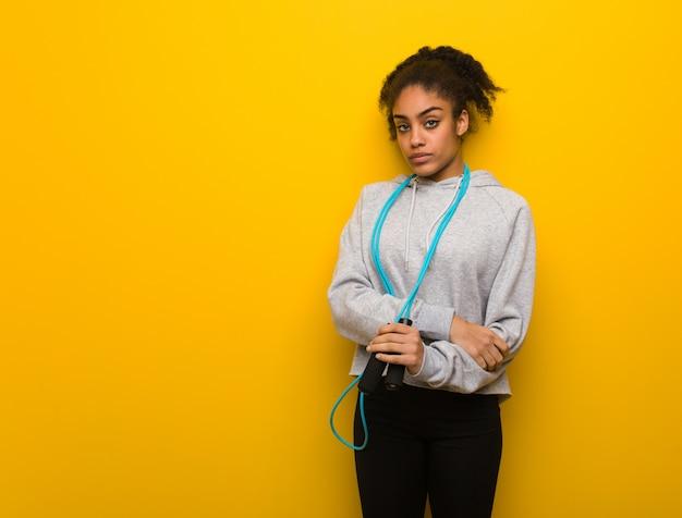 Femme noire jeune fitness regardant droit devant. tenant une corde à sauter.