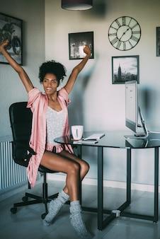 Femme noire à la maison qui s'étend avec ordinateur et café le matin