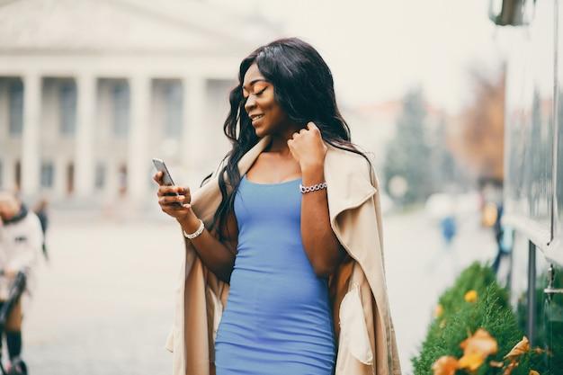 Femme noire marchant dans une ville d'automne