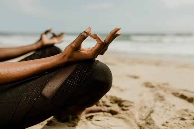 Femme noire méditant sur la plage