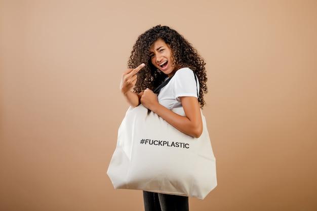 Femme noire millénaire concernée avec un message en plastique de baise écologique sur un sac isolé sur un fond brun