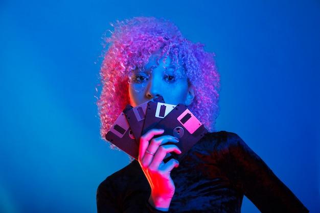 Femme noire millénaire tenant quelques vieilles disquettes