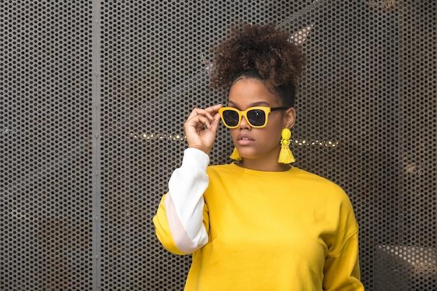Femme noire à la mode en lunettes de soleil jaunes