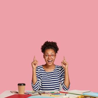Femme noire ravie étonnée avec des cheveux afro peignés en chignon
