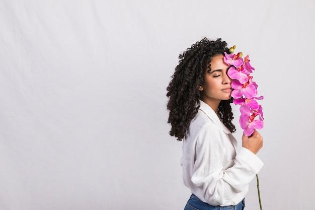 Femme noire réfléchie avec une grande fleur rose
