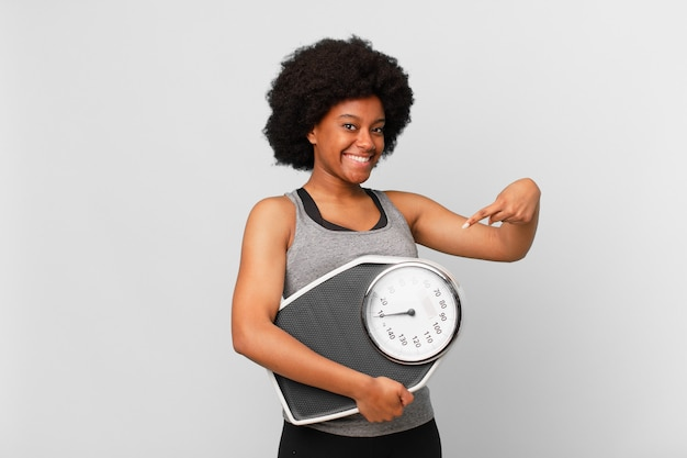 Femme noire de remise en forme afro avec une balance ou une balance