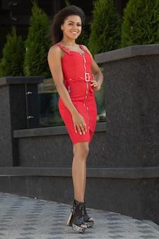 Femme noire en robe rouge en plein air.