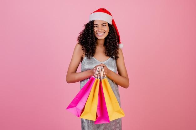 Femme noire avec des sacs à provisions jaunes et roses portant chapeau de noël isolé
