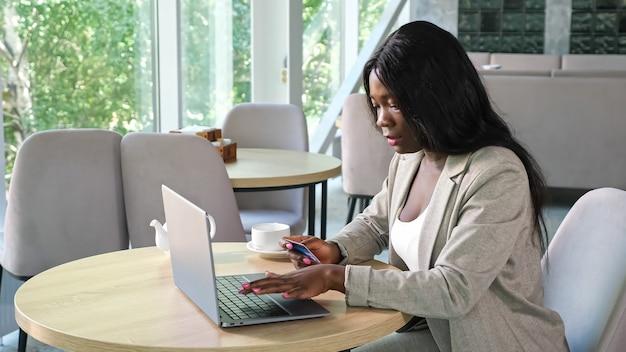 Une femme noire saisit un numéro de carte de crédit pour payer en ligne dans un café