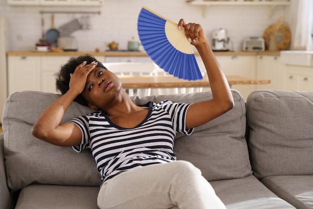 Femme noire souffrant d'un coup de chaleur à plat sans climatiseur agitant un ventilateur allongé sur un canapé à la maison