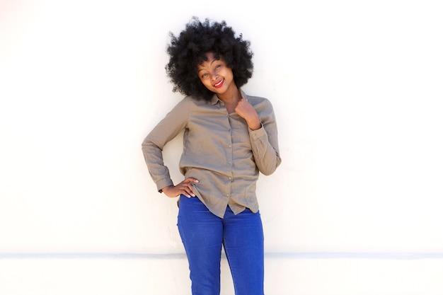 Femme noire souriante debout avec la main au col de la chemise
