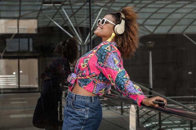 Femme noire souriante, écouter de la musique dans des écouteurs dans la rue
